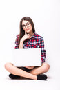 Young woman working on her laptop sitting on the floor over sparse white background Royalty Free Stock Photos