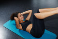Young woman working out at fitness center doing crunch abdominal sit-ups