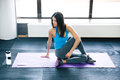 Young woman working out on yoga mat at gym looking away Royalty Free Stock Photos
