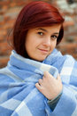 Young woman wrapped in blue blanket, outdoors Royalty Free Stock Photo
