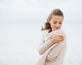 Young woman wrapping in sweater on coldly beach Royalty Free Stock Photo