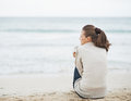 Young woman wrapping in sweater while sitting on lonely beach with long hair Royalty Free Stock Photos