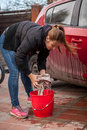 Young woman wringing rag while washing car outdoor photo of Royalty Free Stock Photo