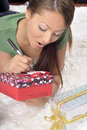 Young woman writing on a gift card on a carpet Stock Photos