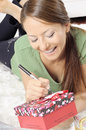 Young woman writing on a gift card on a carpet closeup portrait of Stock Photo