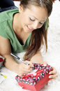 Young woman writing on a gift card on a carpet closeup portrait of Royalty Free Stock Images