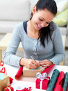 Young woman writing on a gift card on a table Stock Photography