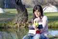 Young woman writing and reading a book in an autumn park Royalty Free Stock Photo