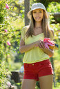 Young woman in yard gardening casual dressed with flowers Stock Photography