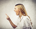 Young woman yelling and pointing her finger Stock Images