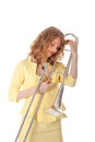 Young woman in yellow mini dress holding trombone against white background Royalty Free Stock Photo