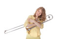 Young woman in yellow mini dress holding trombone against white background Royalty Free Stock Photos