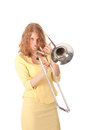 Young woman in yellow mini dress playing the trombone against white background Stock Photo