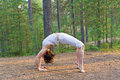 Young woman in Yoga bow pose in the forest Stock Photography