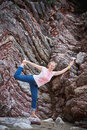 Young woman in a yoga pose on rock background