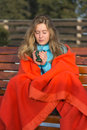 Young women in a blanket blows in her hot coffe on a chilly wint woman sitting bench covered winter morning Royalty Free Stock Photography