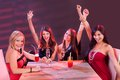 Young women celebrating in a nightclub glamorous sitting around table laughing and raising their arms the air jubilation Stock Photos