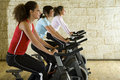 Young women on exercise bikes Stock Photos