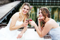 Young Women in Gowns Sharing a Drink Royalty Free Stock Image