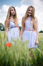 2 young women happy smiling blond girl friends walking in green field & looking at camera over summer outdoors blue sky Royalty Free Stock Photo