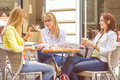 Young women have coffee break together three in street cafe caucasian female relaxing on beautiful summer day in the city Royalty Free Stock Photo