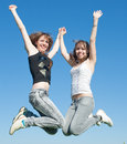 Young women in jeans jumping outdoors Stock Photo