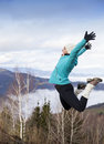 Young women joyfully jumping outdoors sportive woman in the mountains with blue cloudy sky in background Stock Images