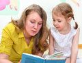 Young women little girl reading book Royalty Free Stock Images