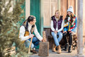 Young women looking at handsome man chopping firewood with axe on porch Royalty Free Stock Photo