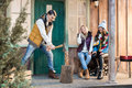 Young women looking at handsome man chopping firewood on porch Royalty Free Stock Photo