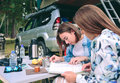 Young women looking road map with x on beautiful friends in a campsite their vehicle tent in the roof the background Stock Photos