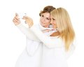 Young women with a mobile phone two pretty in winter clothes on white background Stock Images