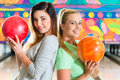 Young women playing bowling and having fun Stock Photography