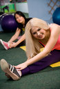 Young women stretching on gym floor Stock Image