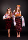 Young women in ukrainian clothes with garland and round loaf on black background Stock Photos