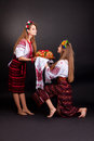 Young women in ukrainian clothes with garland and round loaf on black background Royalty Free Stock Photos