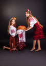 Young women in ukrainian clothes with garland and round loaf on black background Royalty Free Stock Images