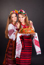 Young women in ukrainian clothes with garland and round loaf on black background Royalty Free Stock Image