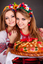 Young women in ukrainian clothes with garland and round loaf on black background Stock Photo