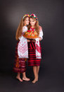 Young women in ukrainian clothes with garland and round loaf on black background Royalty Free Stock Photography