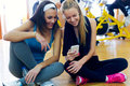 Young women using mobile phone in the gym portrait of Stock Image