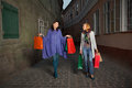 Young women walking on the street with shopping bags in their hands Royalty Free Stock Photos