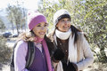 Young women in warm clothes smiling two multiethnic standing outdoors Stock Photo