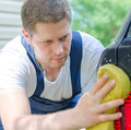 Young worker washing car with yellow sponge Royalty Free Stock Photos