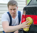 Young worker washing car with yellow sponge Royalty Free Stock Images