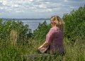 A young 40 years old fat woman sits on a bench in a clearing above the Volga River Russia Royalty Free Stock Photo