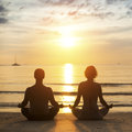 Young yoga couple is meditating in the lotus position on the sea beach during sunset Royalty Free Stock Photography