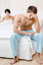 Young young married couple quarrels in bed depressed man sitting on the edge of the focus on man Royalty Free Stock Photo