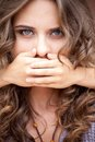 Younger sister closed mouth of her older sister by hands don t tell Royalty Free Stock Images