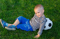 Youngster lying against his soccer ball Royalty Free Stock Image